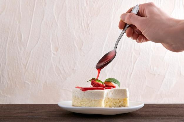 チーズケーキにベリーシロップといちごをかけます