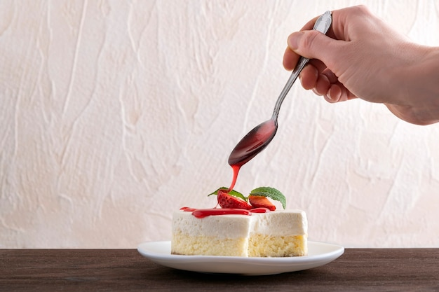 Cheesecake is poured over with berry syrup and strawberry