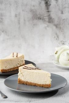 Чизкейк нью-йорк или классический чизкейк с чашкой кофе на белом столе. крупным планом вид. вкусный завтрак. кусок пирога на черной плите, белой чашке на белой мраморной предпосылке. вертикальное фото.
