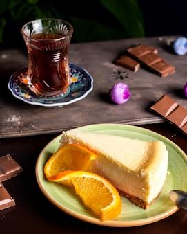Cheesecake servito con una fetta d'arancia e un bicchiere di tè