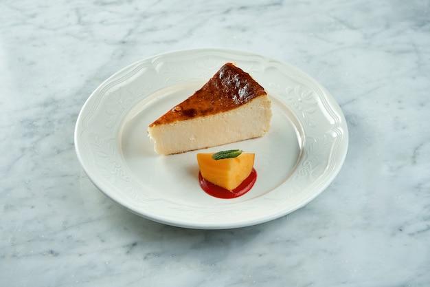 チーズケーキスライス、大理石のテーブルの上の白いプレートで提供されるニューヨークスタイルの古典的なチーズケーキ