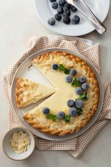 밝은 배경 위에 있는 칼 붙이와 블루베리와 아몬드 플레이크를 곁들인 치즈 케이크 조각