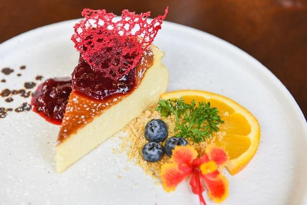 白い皿にラズベリーソースとチーズケーキのスライス