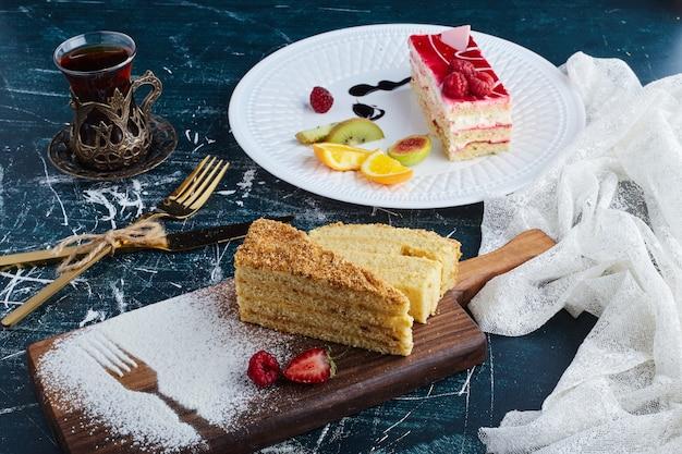 お茶のグラスと白いプレートにラズベリーシロップとチーズケーキスライス。