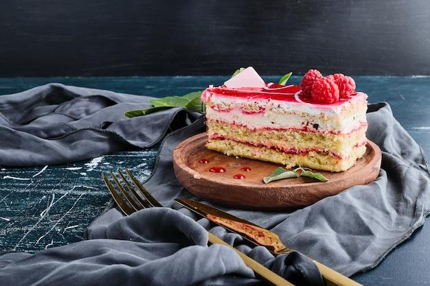 Fetta di cheesecake con sciroppo di lamponi isolato su sfondo blu su un piatto di legno.