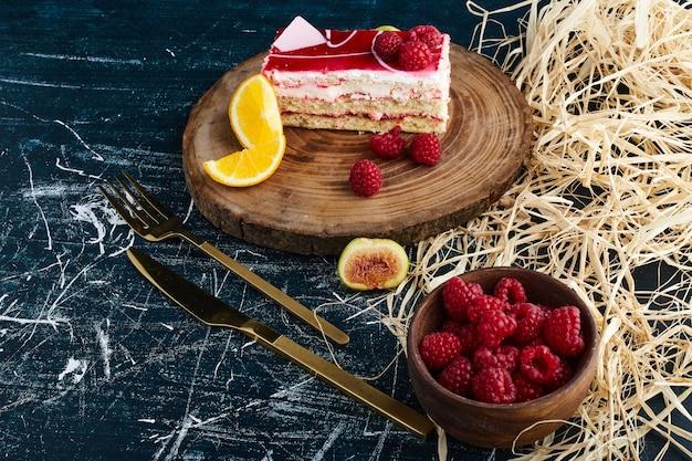 ラズベリーシロップとベリーのカップを脇に置いたチーズケーキスライス。