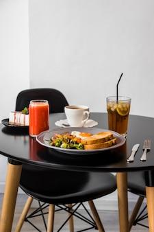 チーズケーキ;スムージーコーヒー;ジュースと黒い丸テーブルの上の朝食