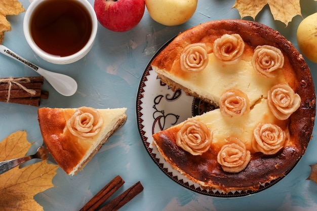 Cheesecake with apples and cup of coffee located on a light blue background, decorated with roses from apples, top view, closeup