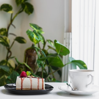 Cheesecake with berries; coffee cup on table in cafe near the plant