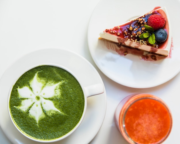 Cheesecake with berries; smoothie and cup of matcha latte art on white background