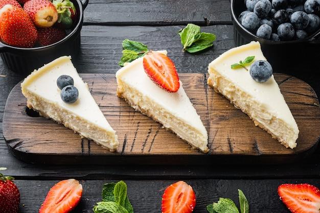 검은 나무 테이블 배경에 블루베리와 딸기가 있는 치즈 케이크