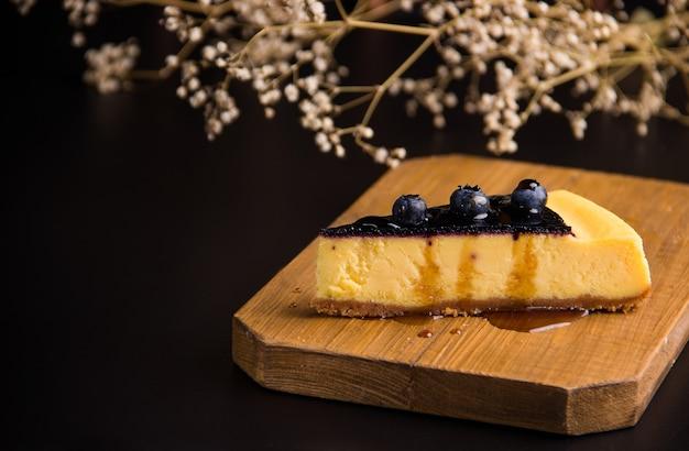 검은 배경에 블루베리와 치즈 케이크입니다. 복사 공간