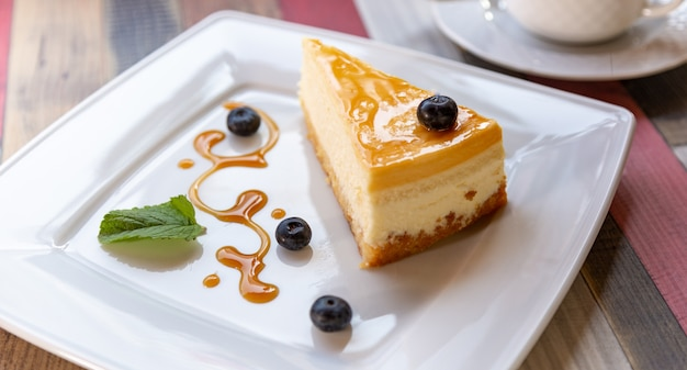 白い皿にブルーベリーソースと木製のテーブルの上のコーヒーカップのチーズケーキ