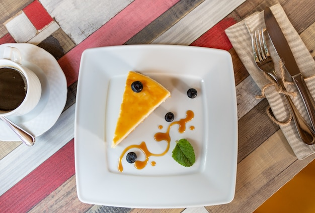 Cheesecake with blueberry sauce on white plate and cup of coffee on wooden table