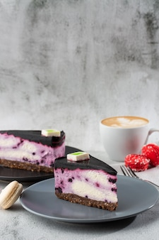 Чизкейк с голубикой с чашкой кофе на белой таблице. крупным планом вид. вкусный завтрак. кусок пирога на черной плите, белой чашке на белой мраморной предпосылке. вертикальное фото.