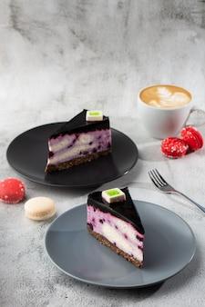 白いテーブルにコーヒーのカップとブルーベリーのチーズケーキ。クローズアップビュー。おいしい朝食。黒い皿にケーキ、白い大理石の背景に白いカップ。縦の写真。
