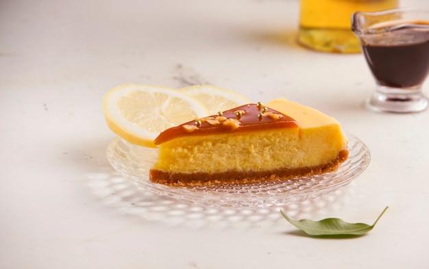 하얀 접시에 카라멜을 곁들인 치즈 케이크