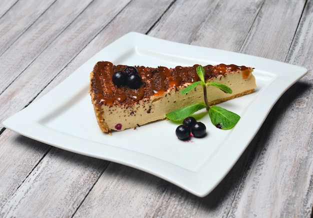 Cheesecake with chocolate on a wooden table.