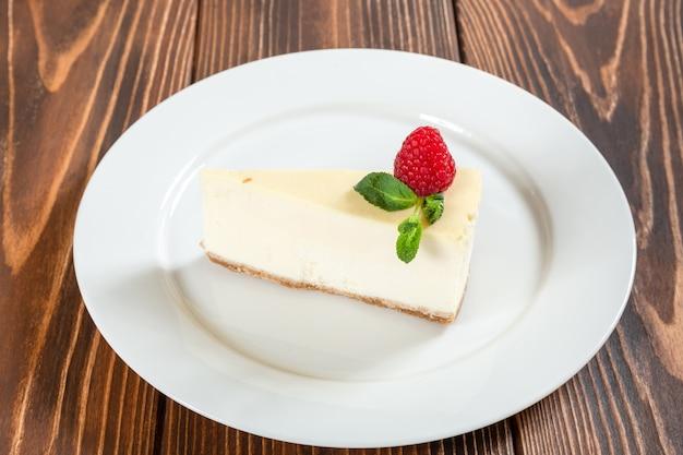 ミントの葉と白いプレート上のイチゴのチーズケーキ