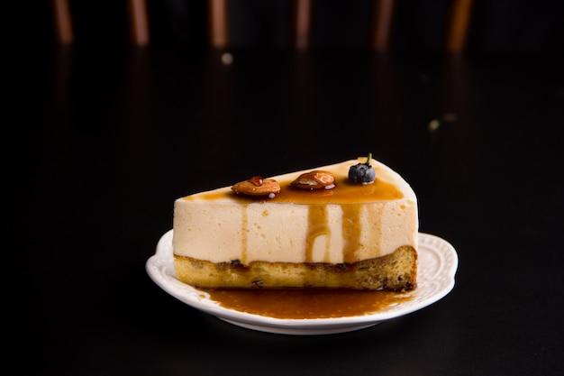 검은 배경에 견과류와 바닐라를 넣은 치즈케이크. 미니멀리즘