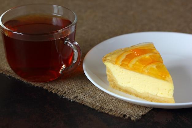 白い皿にオレンジとチーズケーキ、黄麻布のテーブルクロスにお茶とガラスのマグカップ。