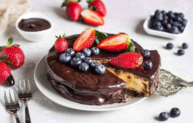 Cheesecake with raisin decorated with chocolate glaze, strawberries and blueberries.