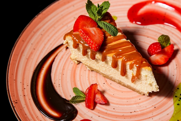 Cheesecake with strawberries on black