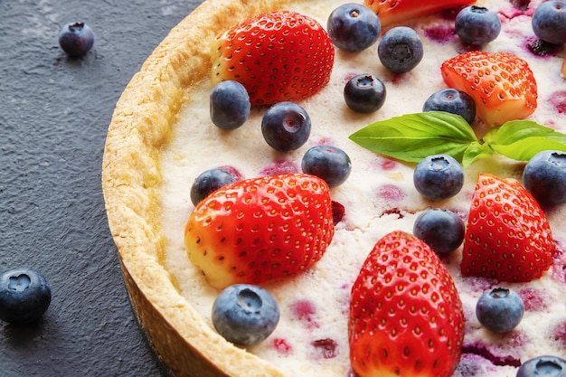 Cheesecake with strawberries and blueberries on concrete background or surface, top view, place copy space, close-up