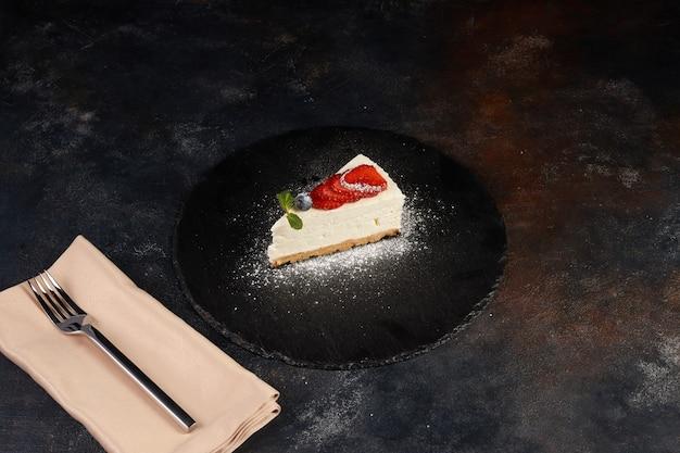 イチゴ、暗い背景のチーズケーキ