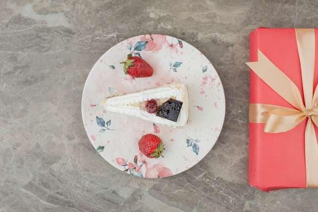 Cheesecake with strawberries and a gift on marble table.