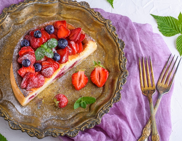 Cheesecake with strawberries on an iron copper plate