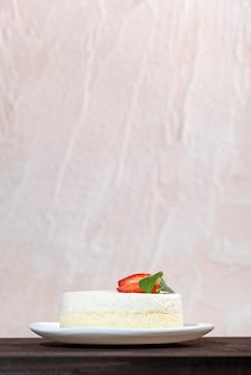 Чизкейк с клубникой на белой тарелке на светлой поверхности