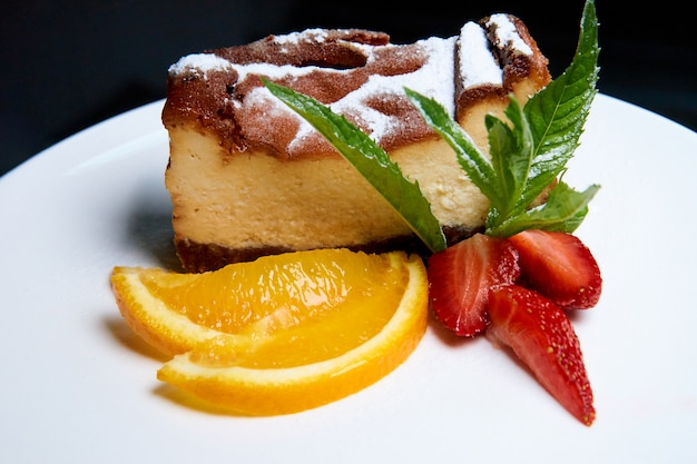 Cheesecake with strawberries and orange slices on a white dish.