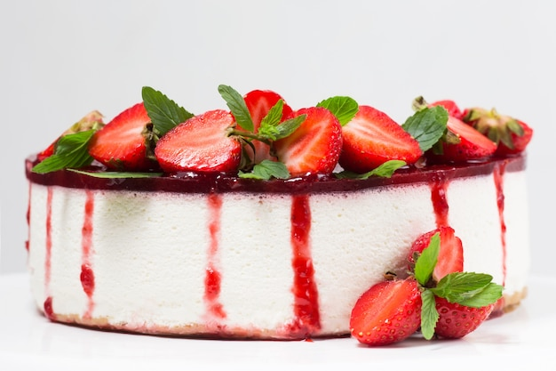 Cheesecake with strawberries on a white plate, fresh berries, mint leaves