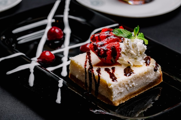 Cheesecake with strawberry cream jam cherry side view