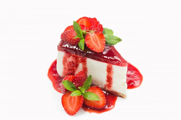 Cheesecake with strawberry jelly and jam, berries, mint leaves isolated