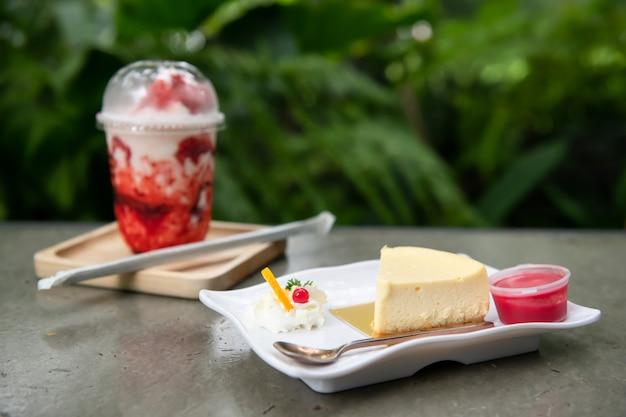 녹색 잎 배경을 가진 테이블에 딸기 소스와 우유 베리 스무디를 곁들인 치즈케이크. 야외 정원 공원에 있는 베이커리와 달콤한 디저트 레스토랑.