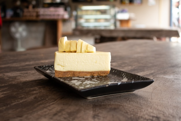 Cheesecake with topped durian fruit and durian cream on wooden desk background. summer fruit for dessert in thailand and asia