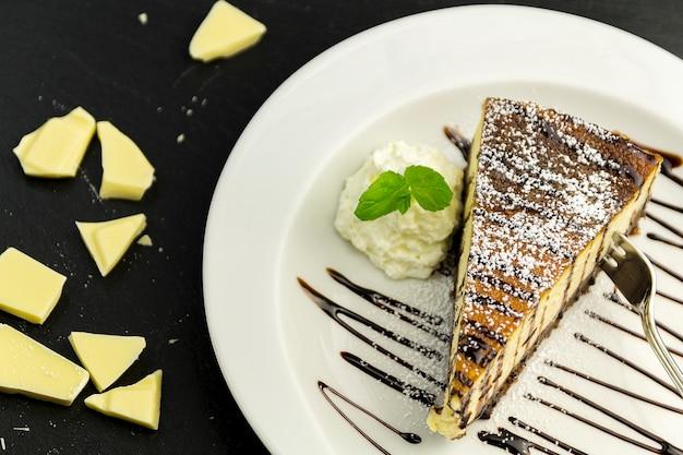 白いプレートと白いチョコレート、黒い背景にホイップクリーム、ミント、チーズケーキ