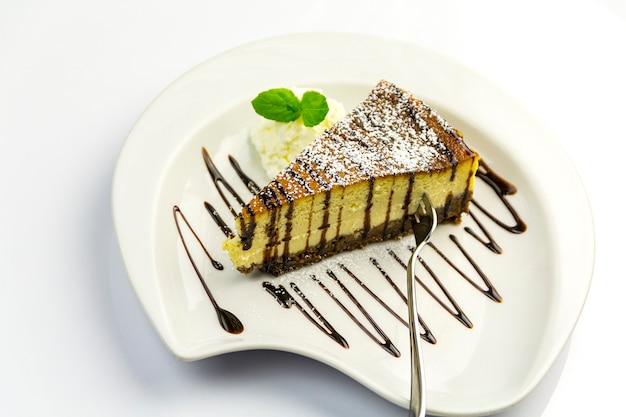 白い皿にホイップクリーム、ミント、チーズケーキ