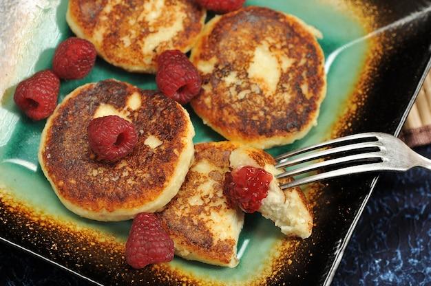 Cheesecakes or cheese pancake with fresh raspberries