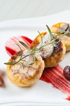 白い皿に粉砂糖、ローズマリーの枝、ベリージャムを添えたブドウで飾られたチーズケーキ。おいしいカッテージチーズの朝食。