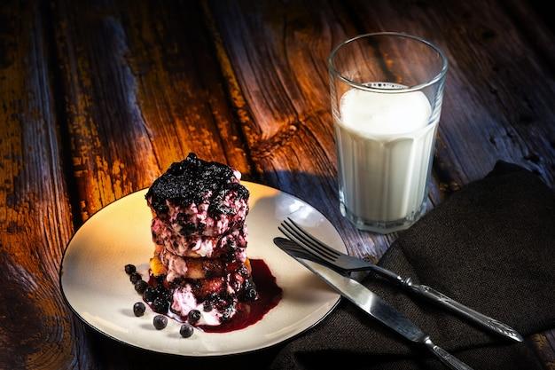 ブルーベリージャムとサワークリームが入ったチーズケーキを皿に載せ、テーブルにミルクを一杯。