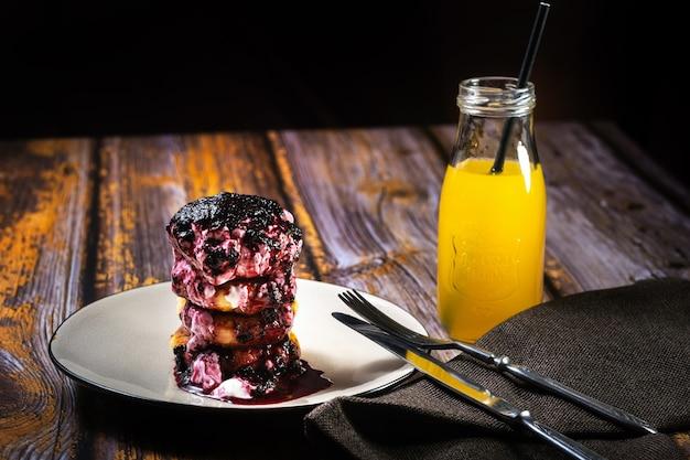 ブルーベリージャムとサワークリームが入ったチーズケーキとオレンジジュースの入ったプレート