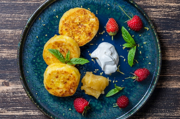 Сырники с мятой, малиной, медом и сметаной. вкусный десерт, украинская кухня. крупным планом, вид сверху