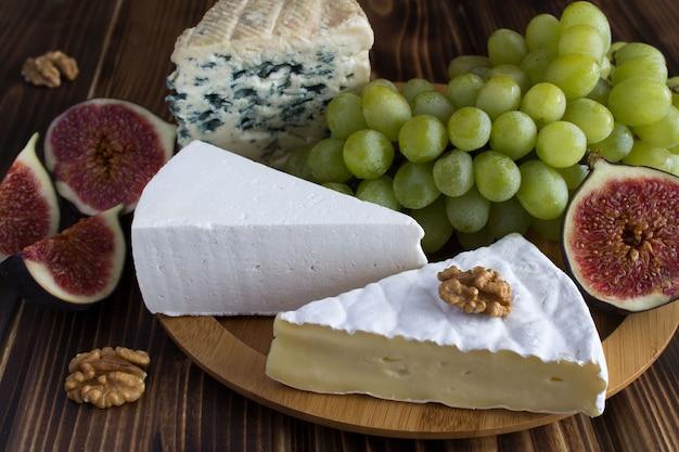 木製の丸いまな板の上のチーズと果物