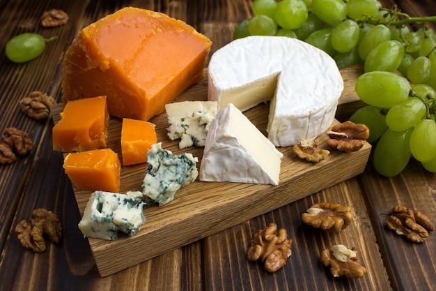チーズ、ブドウ、茶色の木のナッツ