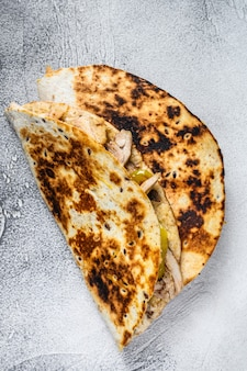 Cheesy chicken roast quesadilla on white table. top view.