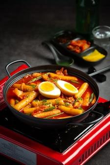 Cibo tradizionale coreano di formaggio tokbokki su priorità bassa nera del bordo. piatto da pranzo.