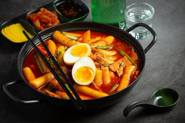 Сырная корейская традиционная еда tokbokki на фоне черной доски. обеденное блюдо.